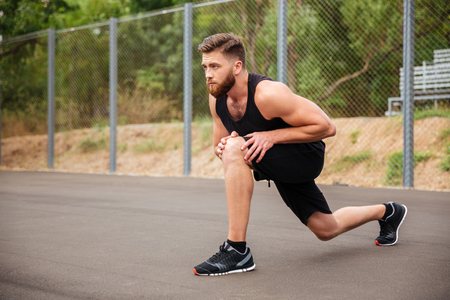 Portrait of a bearded young sports man stretching legs outside Stock Photo