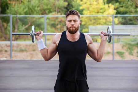Muscular bearded fitness handsome man workout with barbell outdoors