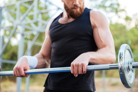 Cropped image of a serious young bearded man athlete exercising and lifting barbell outdoors Stock Photo