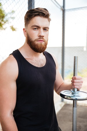 Concentrated young sportsman with barbell looking at camera outdoors Stock Photo
