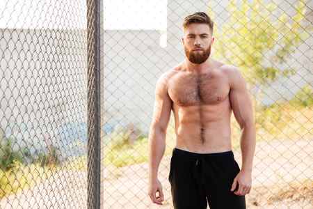 fitness hombre sin camisa apuesto joven durante el entrenamiento al aire libre