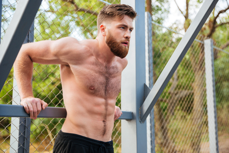 violence in sports: Young concentrated bearded strong man doing sports exercises outdoors Stock Photo