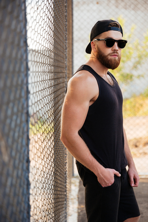 Portrait of handsome sport build man leaning on metal urban fence wearing sunglasses and cap