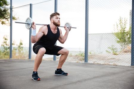 en cuclillas: Concentrado deportivo con barba hombre haciendo ejercicios en cuclillas con la barra al aire libre Foto de archivo