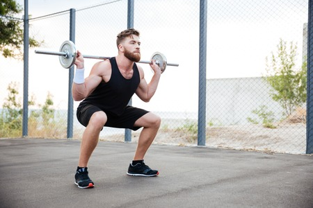 squatting: Concentrated bearded sports man doing squatting exercises with barbell outdoors