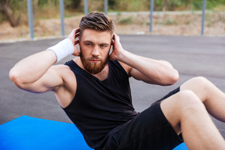 Young bearded sports man doing press exersices on the blue fitness mat outdoors Stock Photo