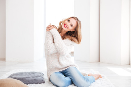 cosy: Smiling charming woman wearing sweater and red lipstick sitting on the carpet at home