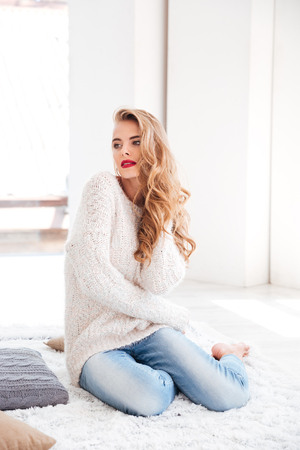 cosy: Beautiful young woman in sweater sitting on the carpet at home Stock Photo