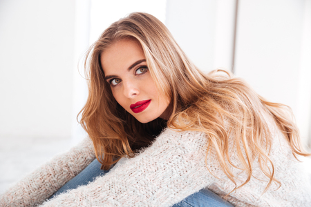 Close up portrait of beautiful blonde woman wearing sweater and red lipstick looking at camera Stock Photo