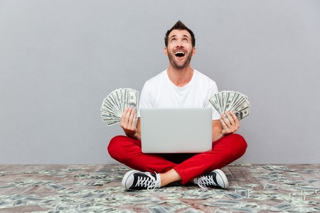 Excited lucky man holding banknotes and sitting on the floor with laptop over gray background