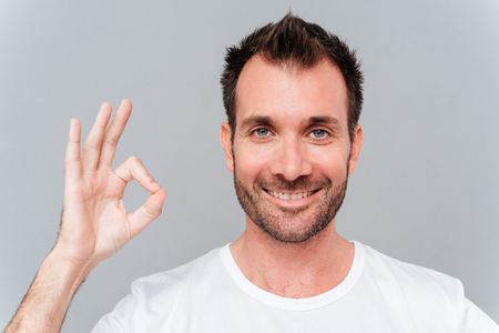 all ok: Happy casual man showing ok sign with fingers isolated on a gray background
