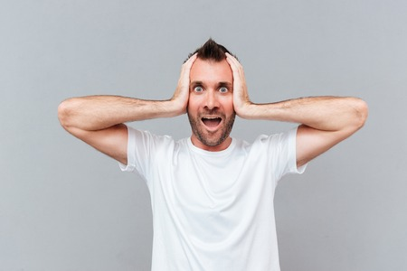 hands over ears: Stressed young man covers ears by hands and shouting over gray background