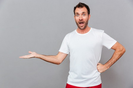 Surprised casual man holding copyspace on a palm over gray background