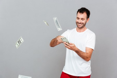 counting money: Handsome young casual man counting money over gray background