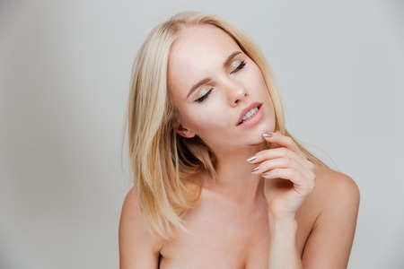girl with gray eyes: Sensual nude blonde girl with closed eyes posing isolated on a gray background Stock Photo