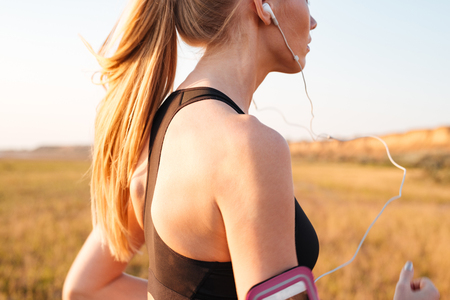 Cropped image of a blonde sports woman running with earphones outdoors 스톡 콘텐츠