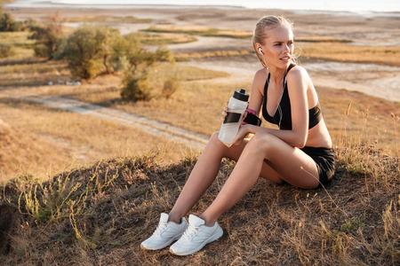 Fitness junge Frau ruht und mit Wasserflasche nach dem Joggen im Freien