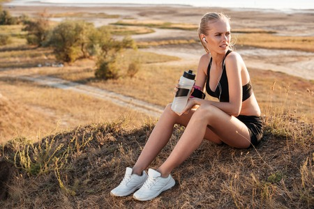 Giovane donna di forma fisica che riposa e che tiene bottiglia di acqua dopo avere pareggiato all'aperto Archivio Fotografico - 65995434