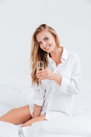 fiancee: Cheerful smiling woman with glass of champagne wearing white shirt in bed Stock Photo