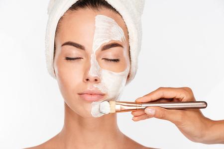 Portret van een aantrekkelijke jonge vrouw die het maskerbehandeling van de schoonheidshuid op haar gezicht met borstel krijgt