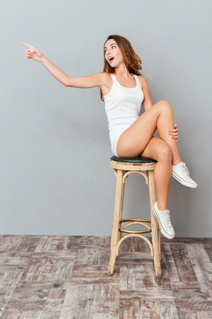 astonishing: Amazed charming woman sitting on the chair and pointing away isolated on gray background