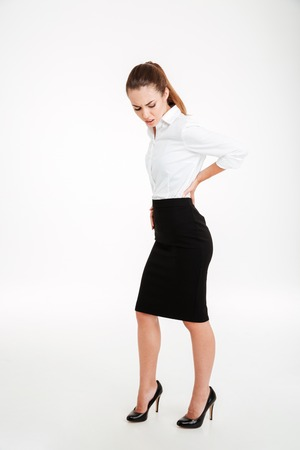 Full length portrait of a stressed businesswoman with back pain isolated on a white background