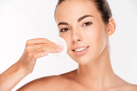 Femme de soin de peau enlever le maquillage du visage avec un tampon de coton-tige isolé sur fond blanc