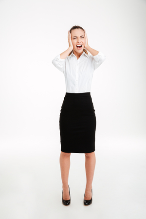 Full length portrait of a young businesswoman covering her ears and shouting over white background Stock Photo