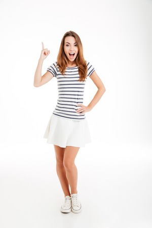 Happy inspired young woman pointing up and having an idea over white background