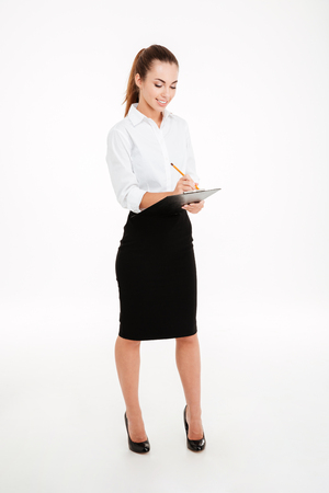 Full length portrait of a friendly young smiling businesswoman with clipboard and pen over white background Stock Photo