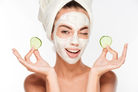 Young woman with clay facial mask holding cucumber slices isolated on white background Foto de archivo