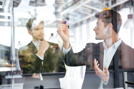 Two concetrated young businessmen talking and writing on glass board in office Stock Photo