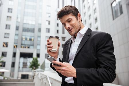 Het glimlachen het jonge zakenman drinken haalt koffie weg en gebruikt celtelefoon in openlucht Stockfoto
