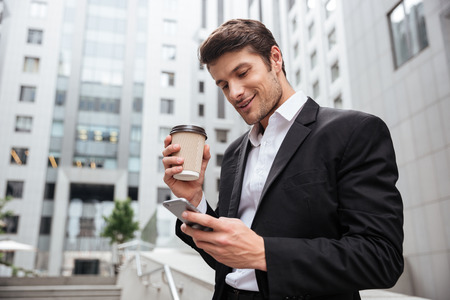 Smiling young businessman drinking take away coffee and using cell phone outdoors