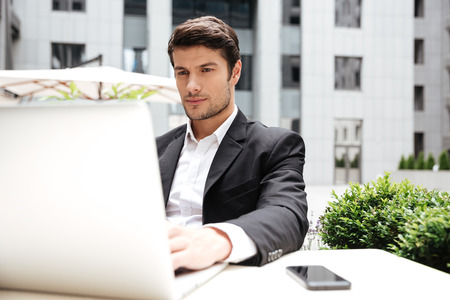 concentrate on: Serious young businessman sitting and using laptop in outdoor cafe