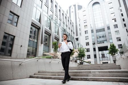 tomando refresco: hombre de negocios joven feliz caminar y tomar café cerca del centro de negocios Foto de archivo