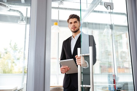 Knappe jonge businesman tablet met het invoeren van de deur in het kantoor