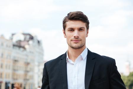 autoridad: Primer plano de negocios joven y guapo en traje de pie al aire libre