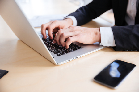 Closeup of hands of young businessman using laptop and blank screen cell phone in office