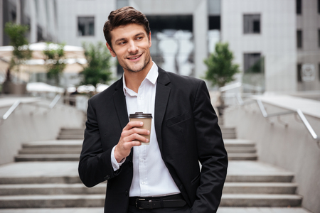 tomando refresco: Happy attractive young businessman smiling and drinking coffee in the city Foto de archivo