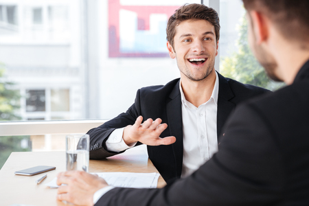 teamworking: Cheerful young businessman talking with his colleague on business meeting