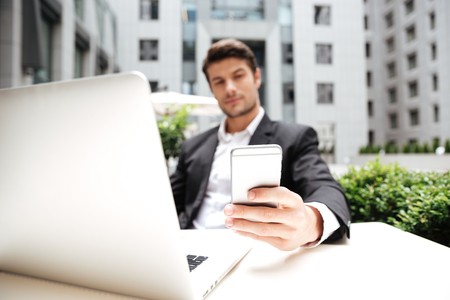 Attractive young businessman using laptop and cell phone in outdoor cafe Stock Photo