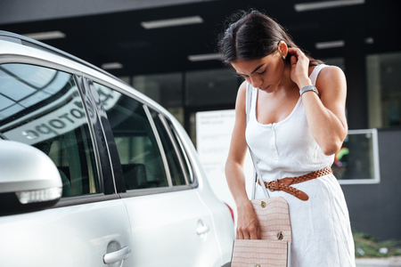 Pretty young woman standing and looking keys of car in her bag outdoors Banque d'images