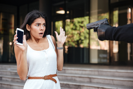 abducted: Scared young woman with blacnk screen cell phone threatened by criminal with gun on the street Stock Photo