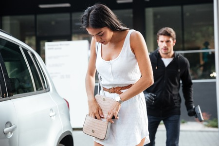 Pretty young woman being stalked by man criminal with gun on outdoor car parking