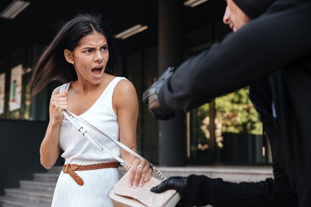 Angry young woman shouting and protecting from man thief with gun on the street Stock Photo