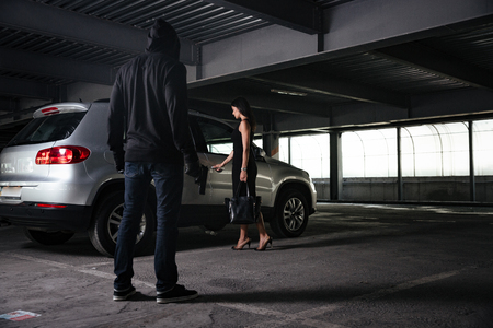 Criminal man in black hoodie standing and looking at young woman opening car on parking