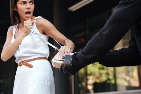 mujer joven irritada gritando y luchando con qué ladrón robar su bolso en la ciudad