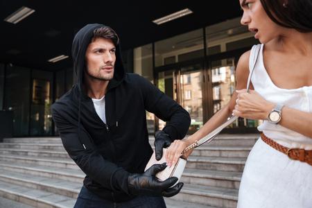 Ladrón hombre en sudadera con capucha negro robar el bolso de la mujer en la calle Foto de archivo - 65836571