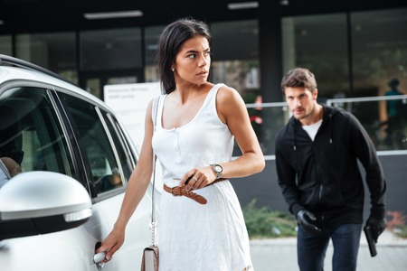 unsuspecting: Dangerous young man robber stalking to young woman opening her car Stock Photo